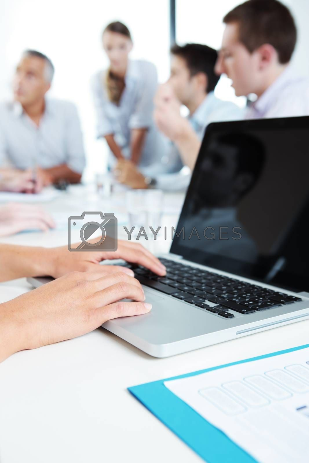 Group of business people working together, hands typing on laptop