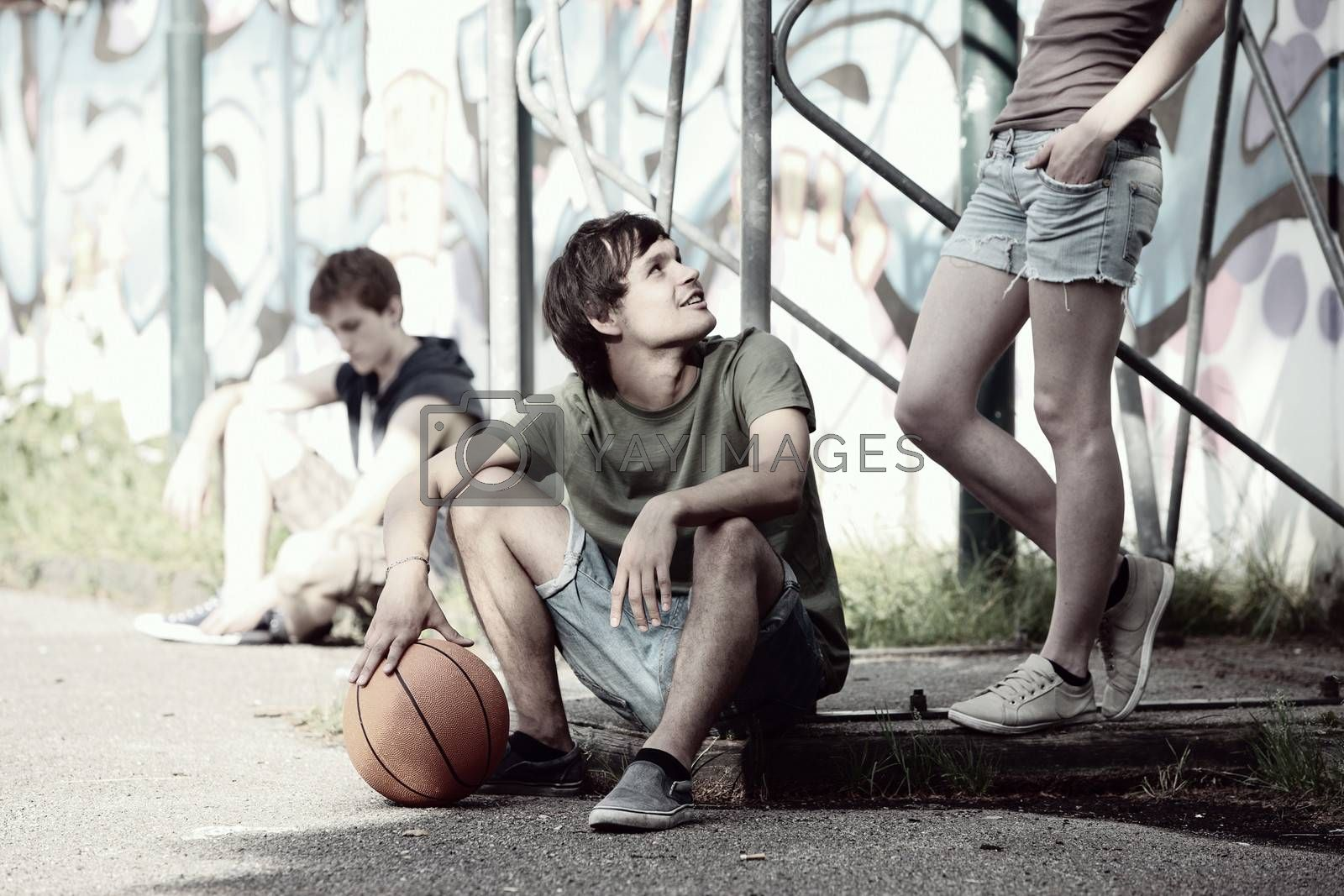 Group of friends taking a break after playing basketball
