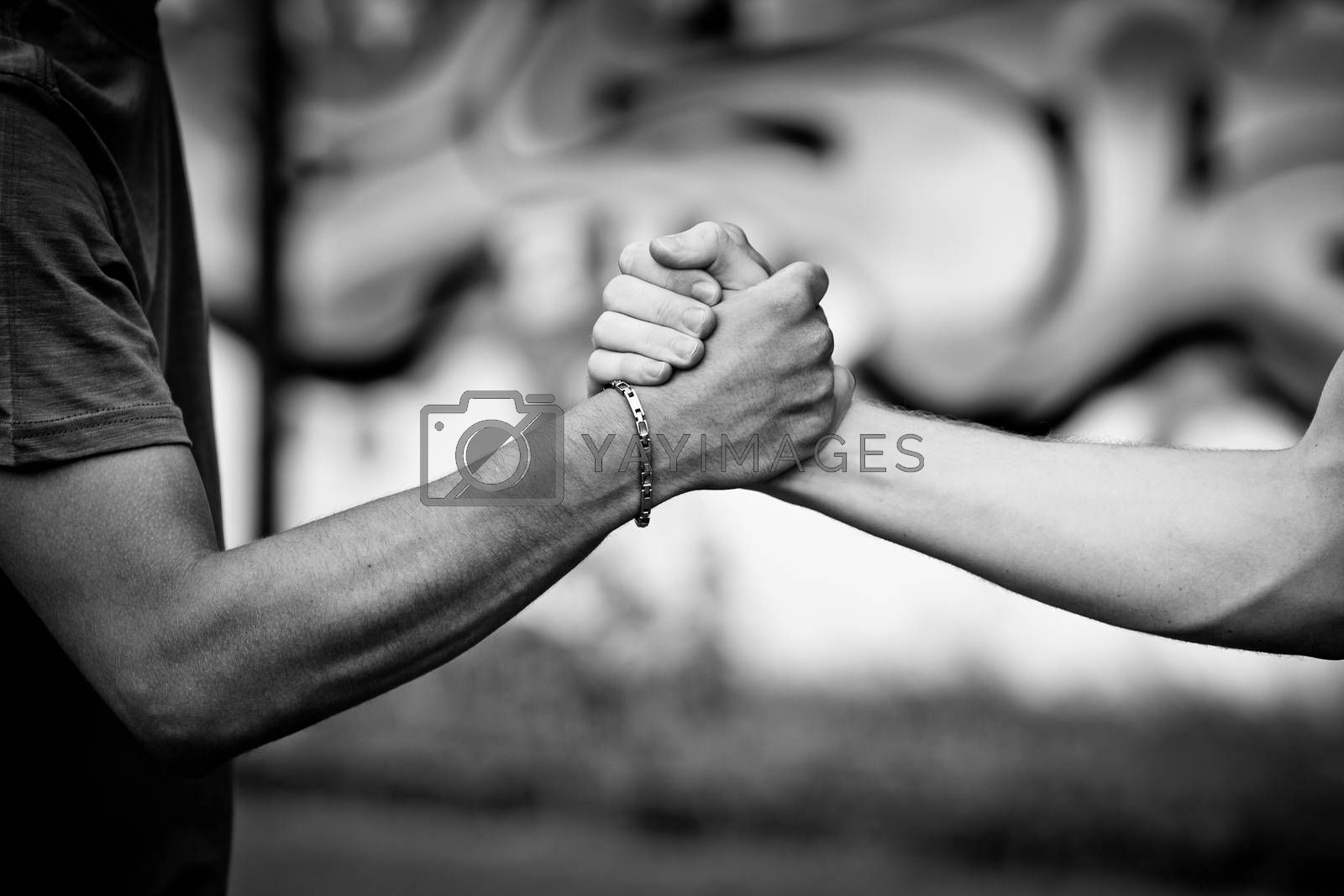 White teen and Black teen clasp hands against a wall with graffiti