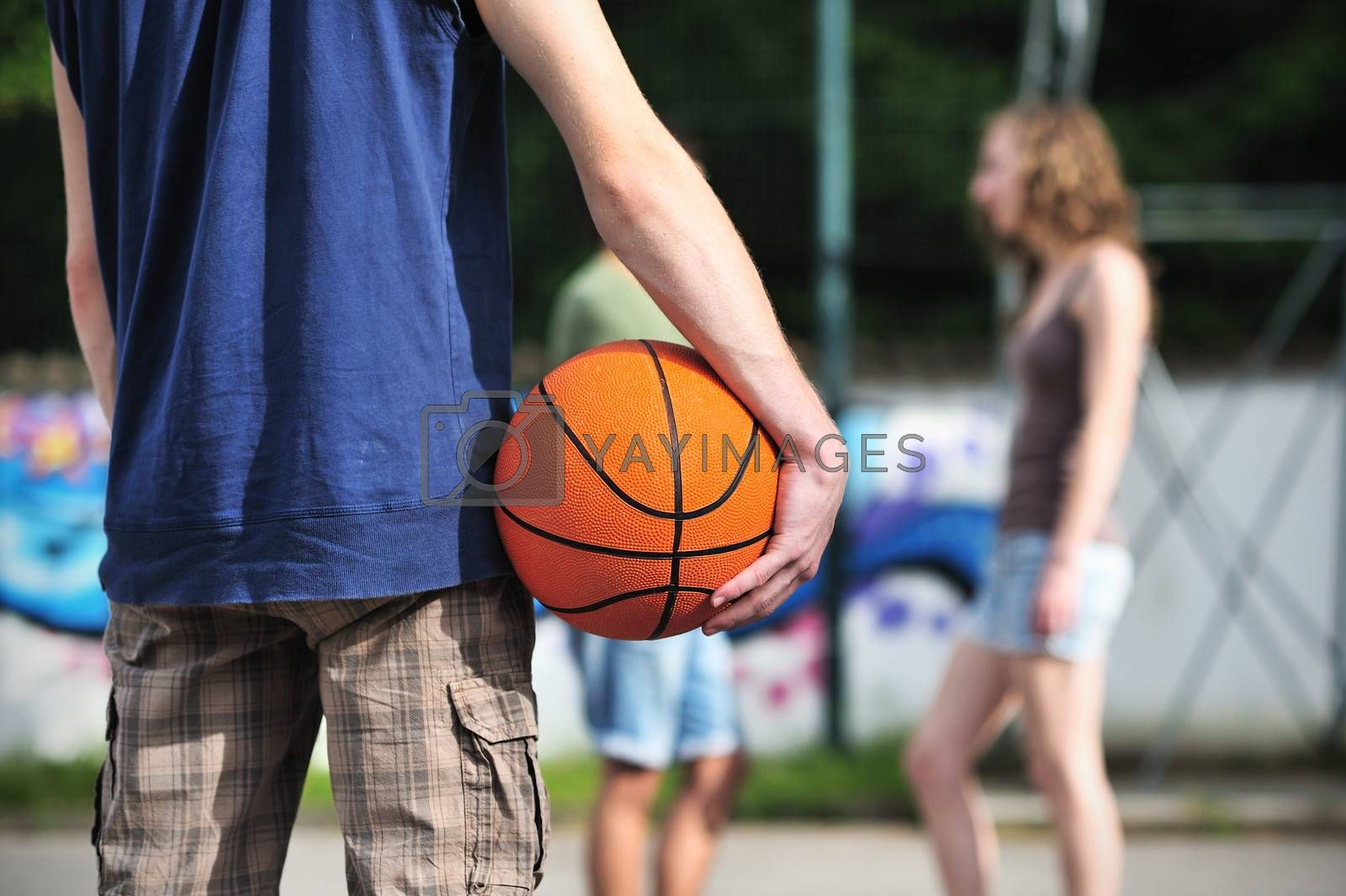 Group of friends talking and taking a break after playing basketball