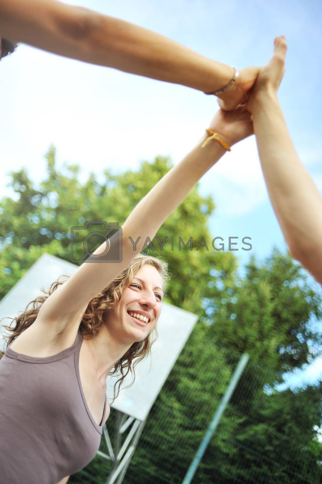 Three teenagers giving a high five, hands close up