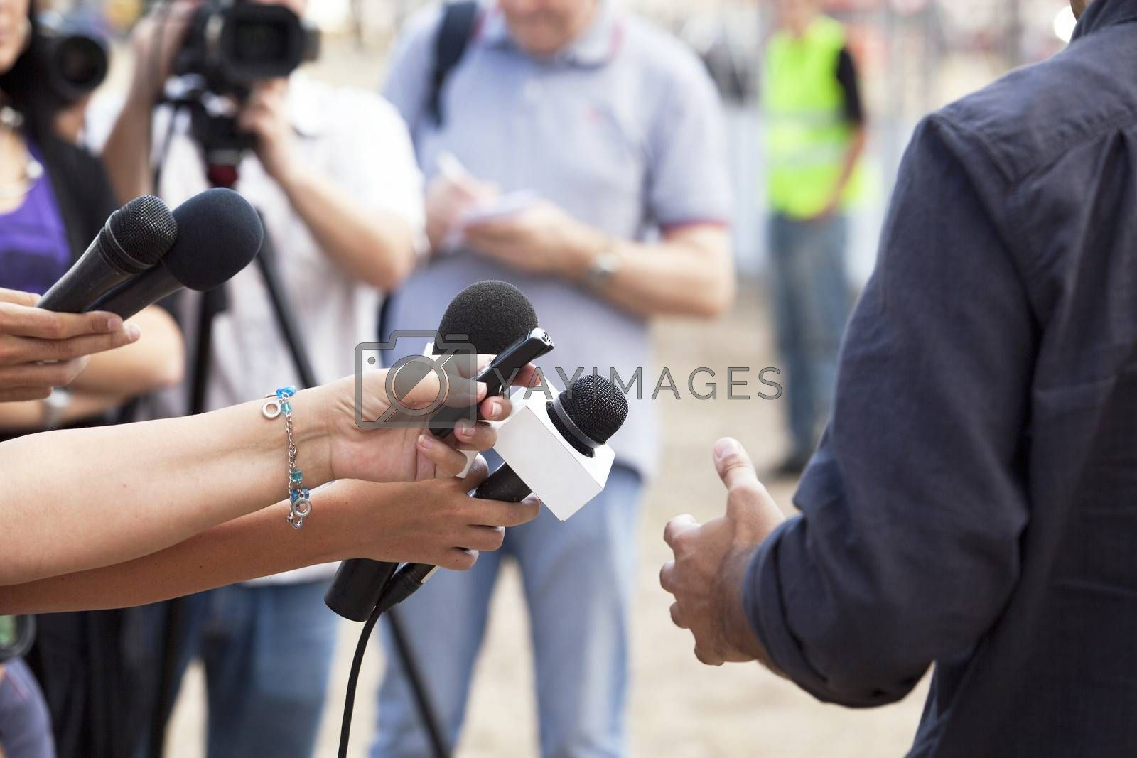 Journalist hand holding a microphone conducting an TV or radio interview