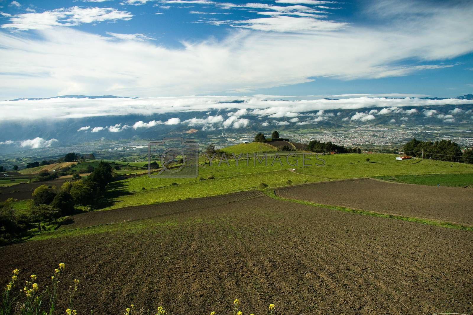 Scenic view of plowed field in countryside field with cloudscape background, Costa Rica.