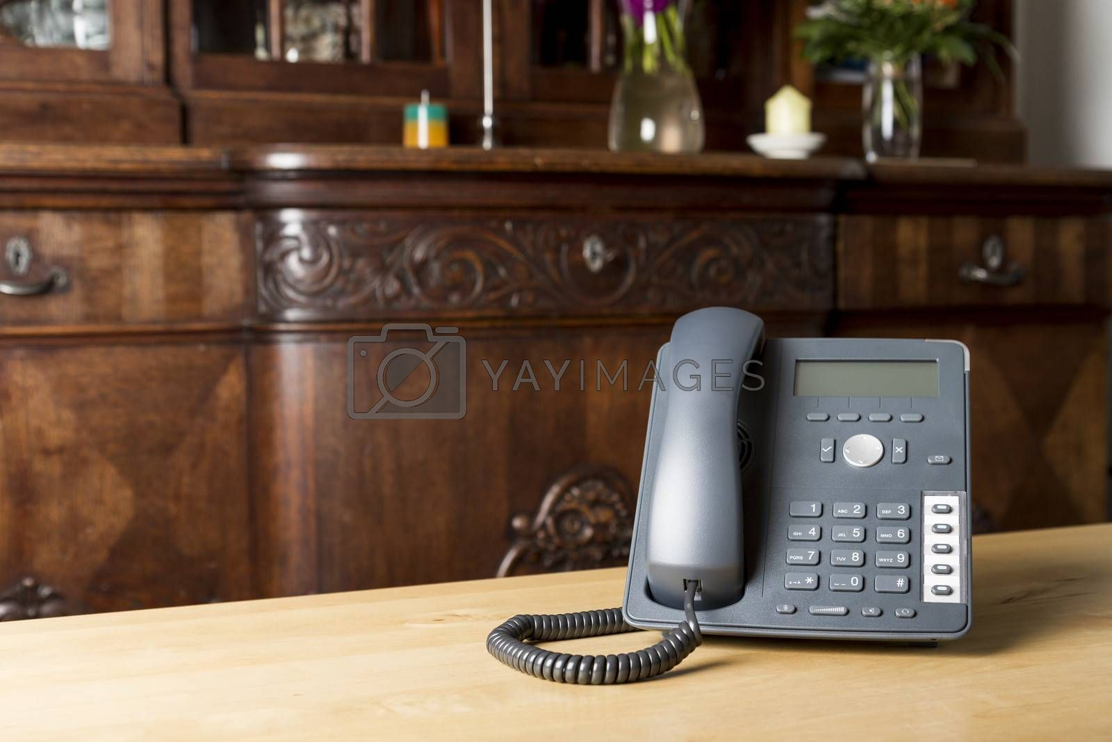 modern phone on wooden table in living room with old commode