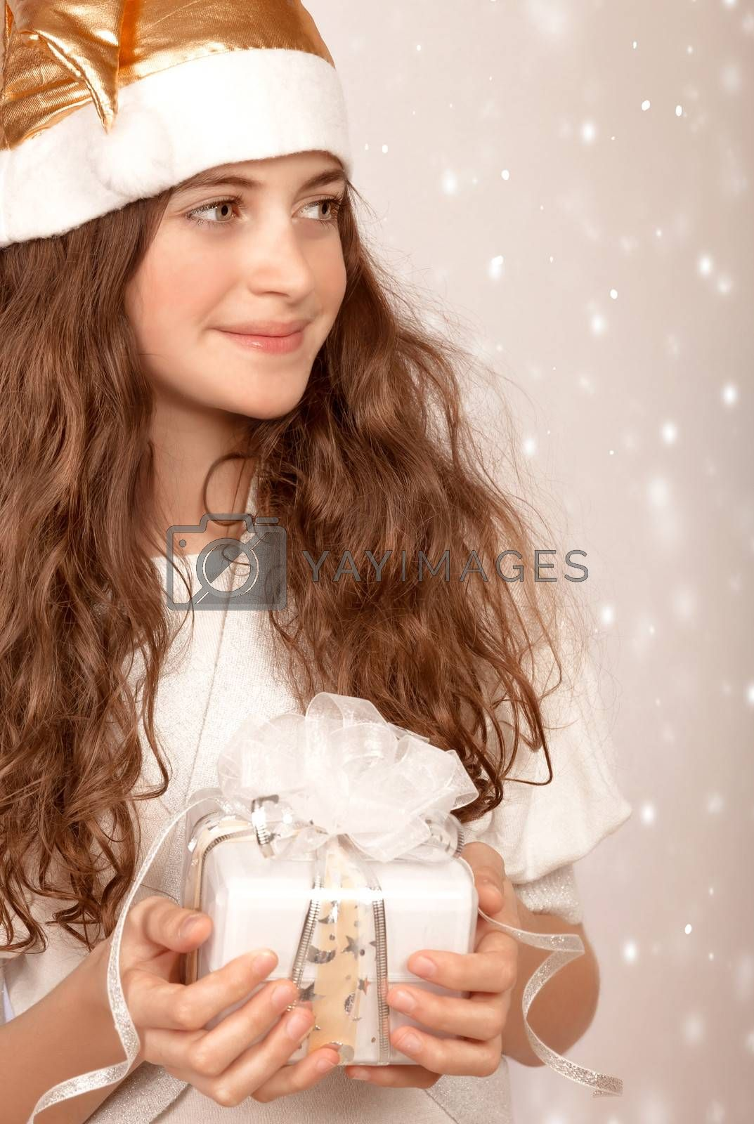 Closeup portrait of beautiful Santa girl holding in hands cute white gift box, wintertime holidays, looking in a side, Christmas joy, happiness concept