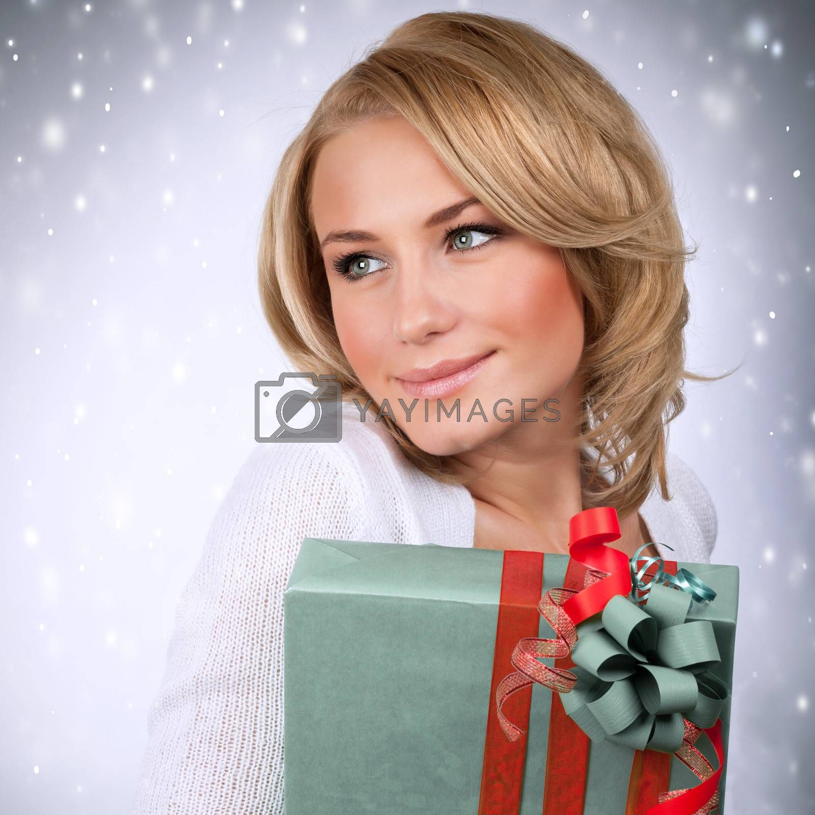 Portrait of sensual blonde girl holding stylish wrapped gift box, Christmas time party, New Year surprise, happiness and enjoyment concept