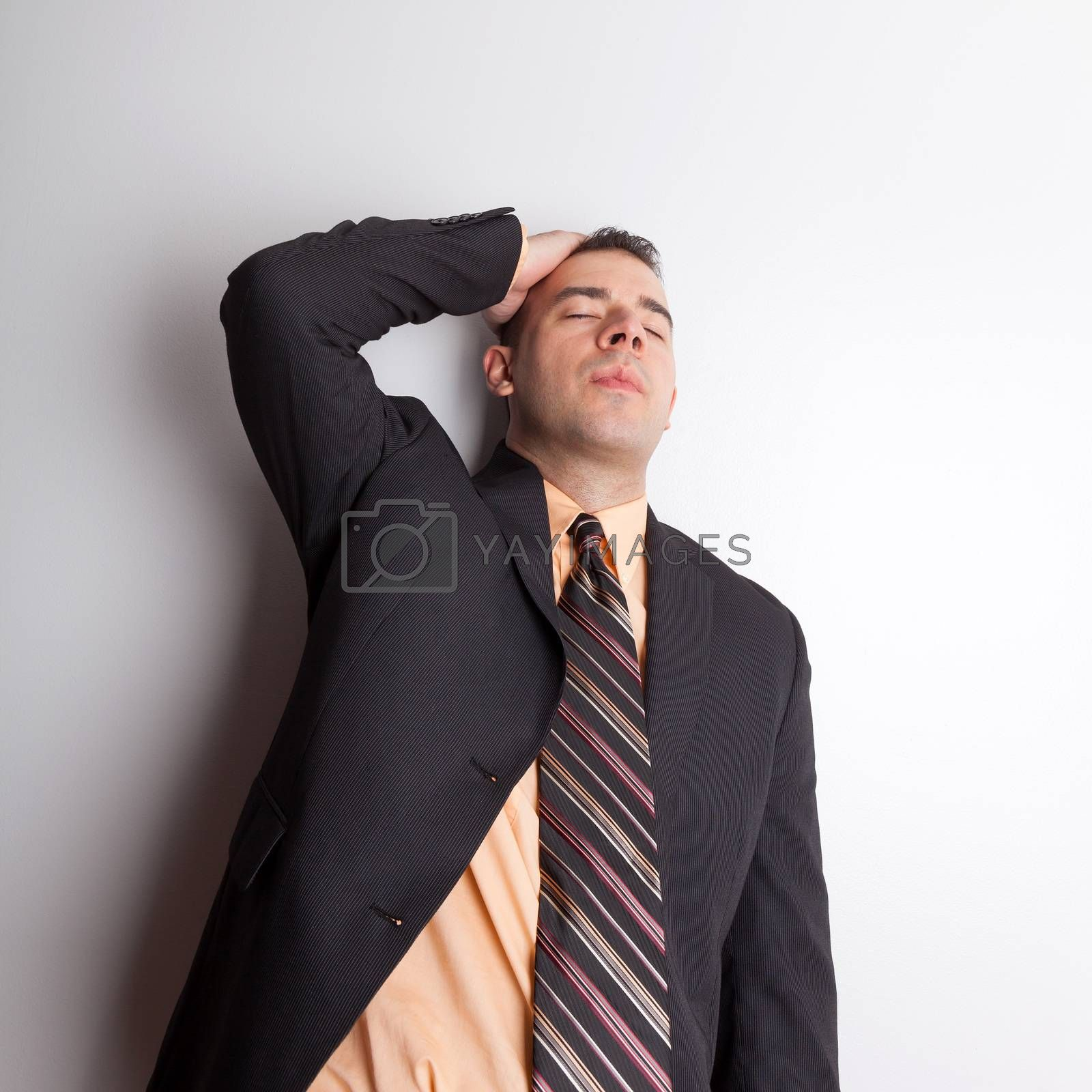Stressed out business man isolated over a silver background worried or depressed about finances and difficult economic times.