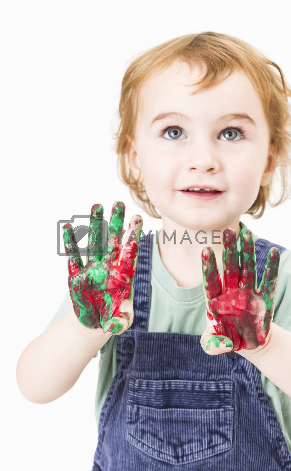 cute little girl with finger paint. vertical image in light grey background