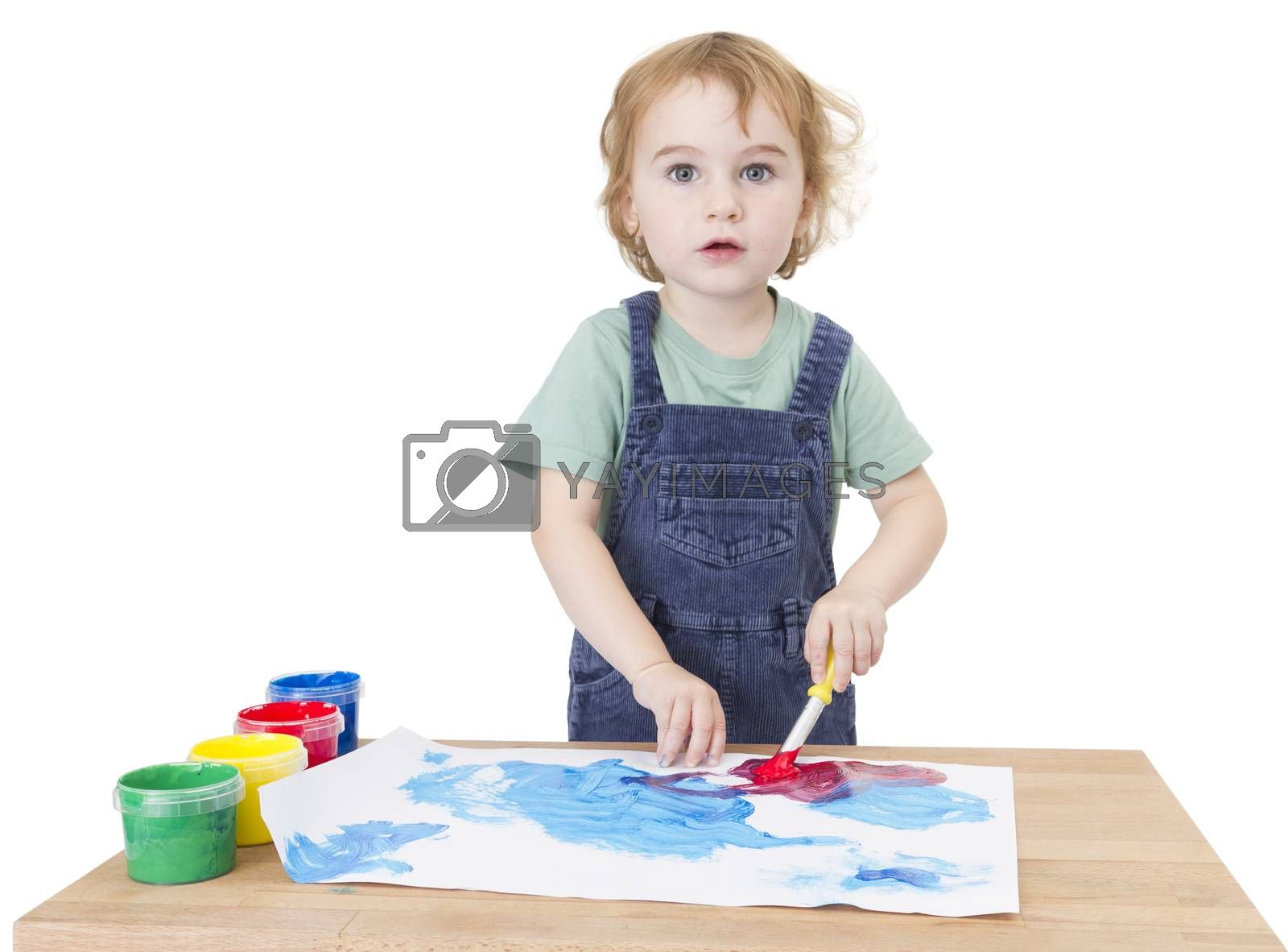 cute girl painting on small desk in white background. studio shot