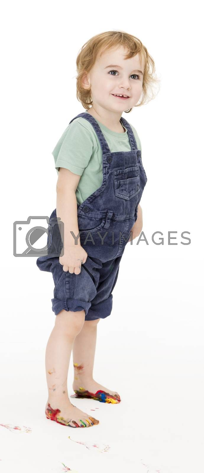 child with painted feet holding trousers up. studio shot in grey background