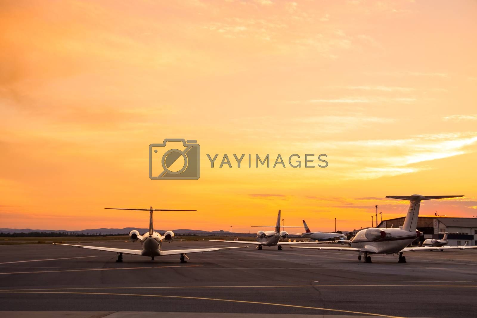 Private airplanes parked at the airport at sunset.