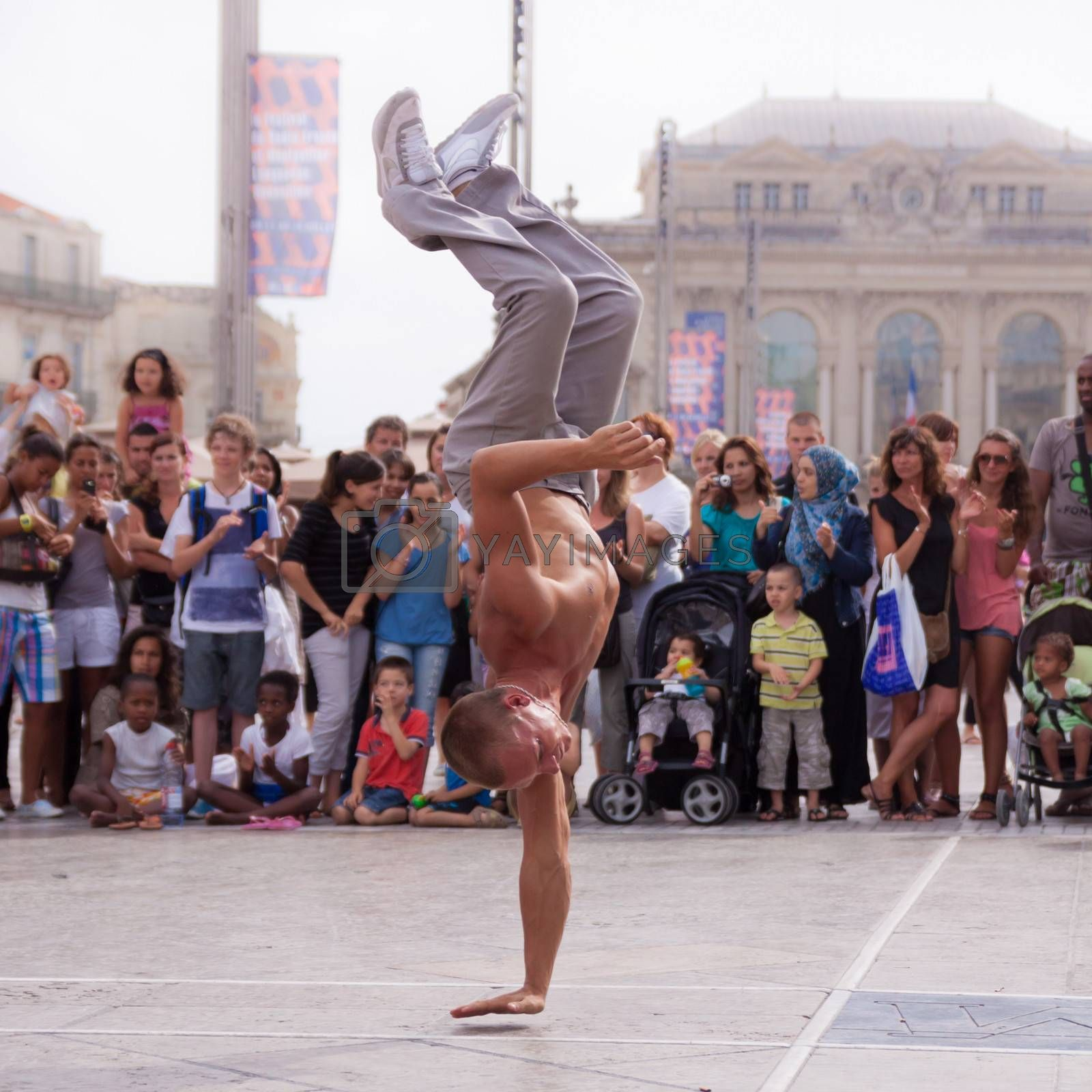 MONTPELLIER - JULY 12: Street performer breakdancing in front of the random crowd on July 12, 2011 in  Montpellier, France; B-boying or breaking is a style of street dance that originated among African American and Puerto Rican youths in New York City during the early 1970s.