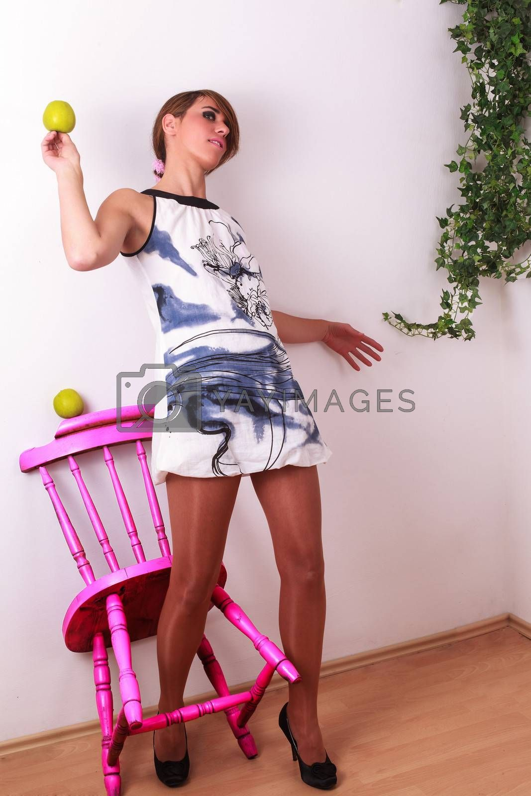Backward to the wall ajar female beauty, with apple in hand, with one leg between the chair legs of a pink chair