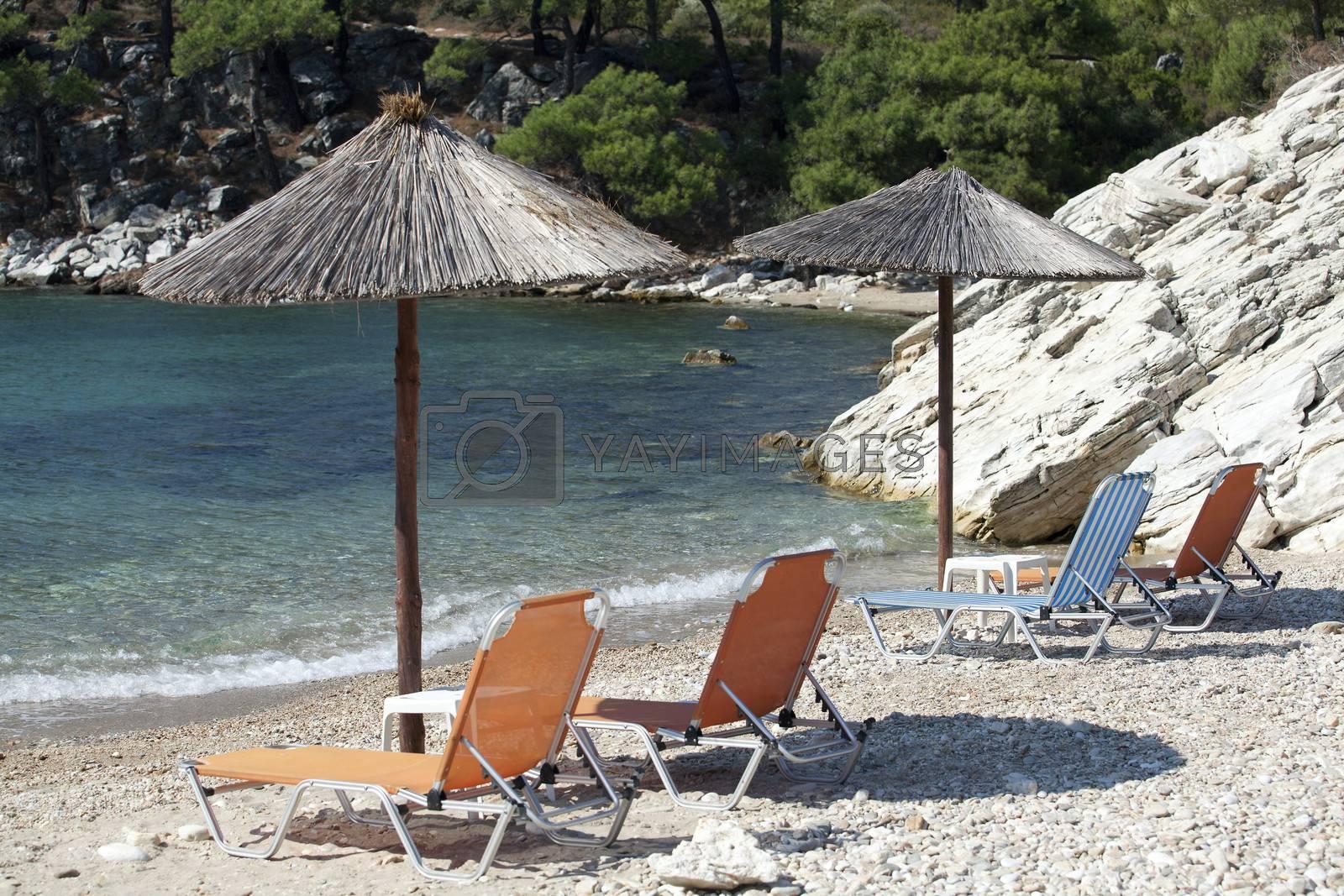 Deckchairs under parasol on sunny beach