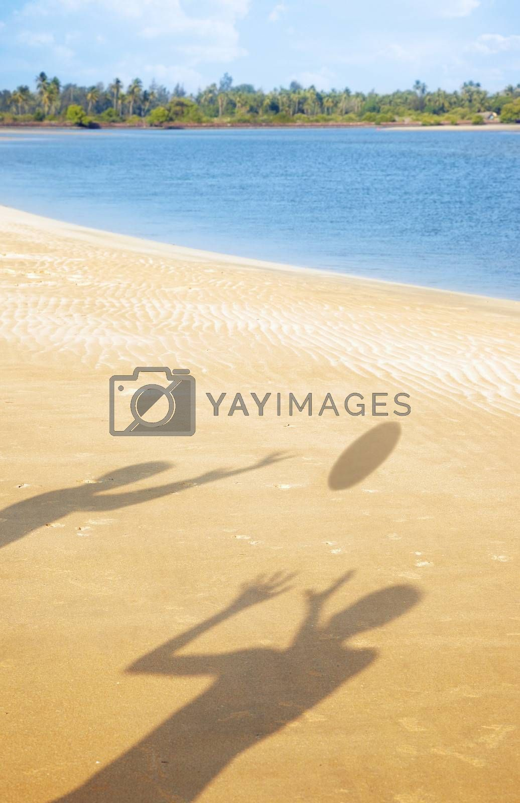 Shadows of two people playing with ball at the summer beach. Vertical photo with vibrant colors