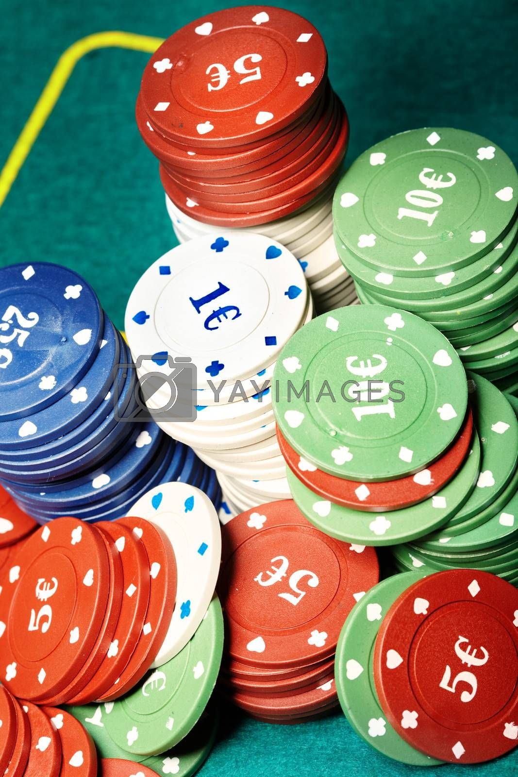 Stack of casino chips on a green casino table. Close-up photo