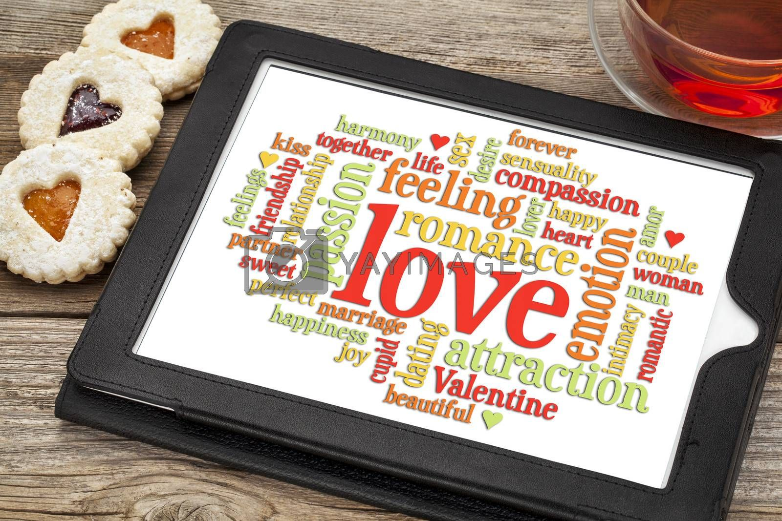 love word cloud on a digital tablet screen with heart cookies and a cup of tea