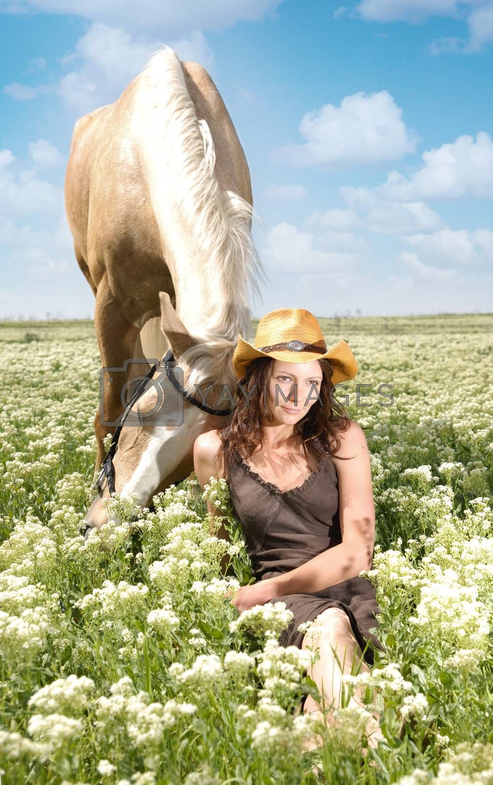 Tender relationship between the horse and lady sitting in the grass
