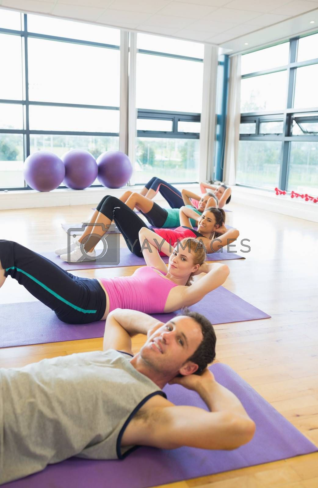 Side view portrait of sporty fitness class doing sit ups on exercise mats