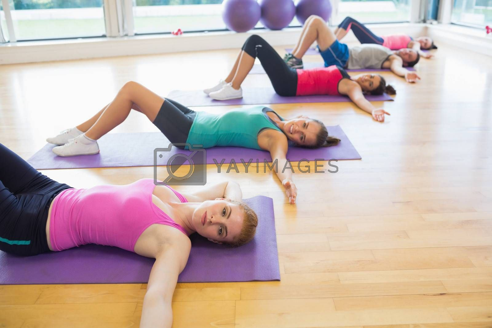 Side view of fitness class lying on exercise mats in row at fitness studio
