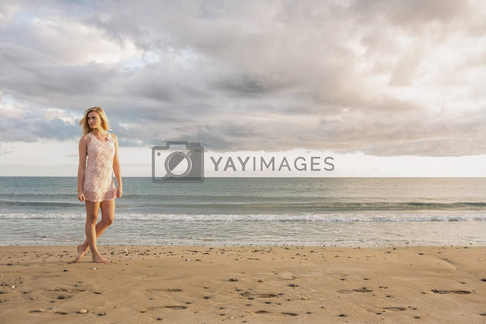 Full length of a pretty young woman in summer dress walking on the beach