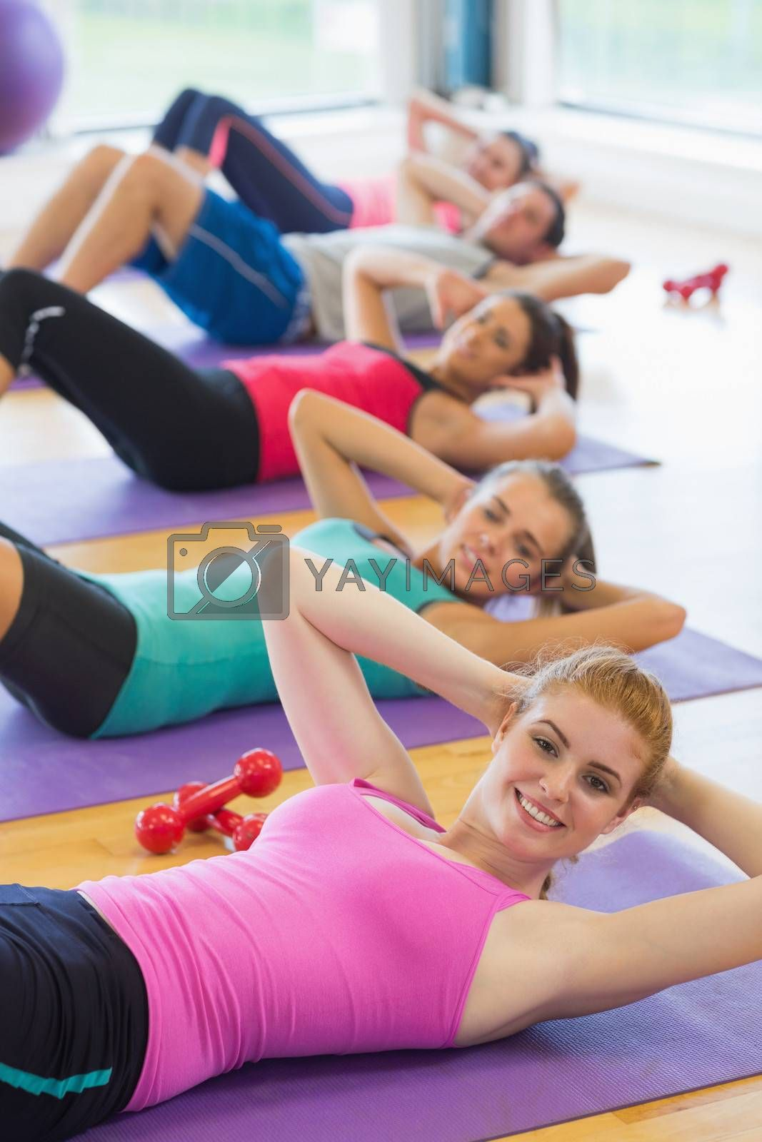 Portrait of sporty fitness class doing sit ups on exercise mats