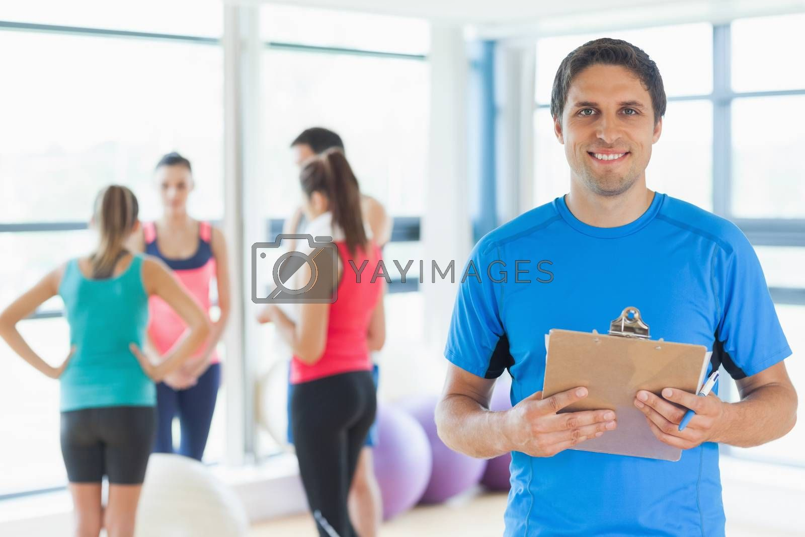 Portrait of an instructor with fitness class in background in fitness studio