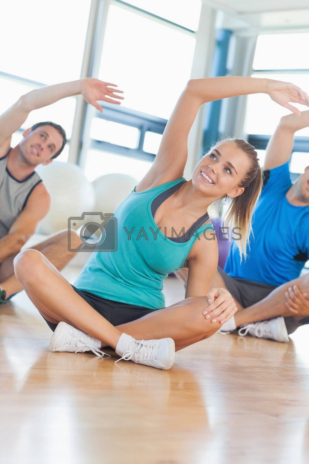 Fitness class and instructor sitting and stretching hands in bright exercise room