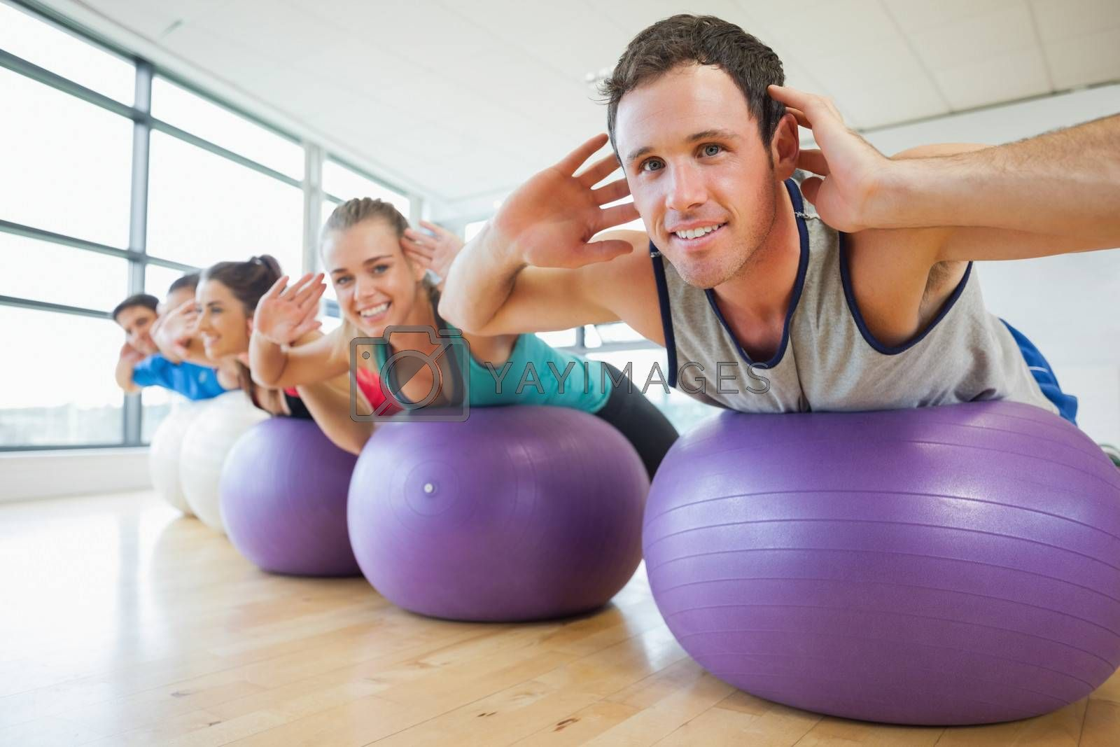 Portrait of class exercising on fitness balls in a row at the bright gym