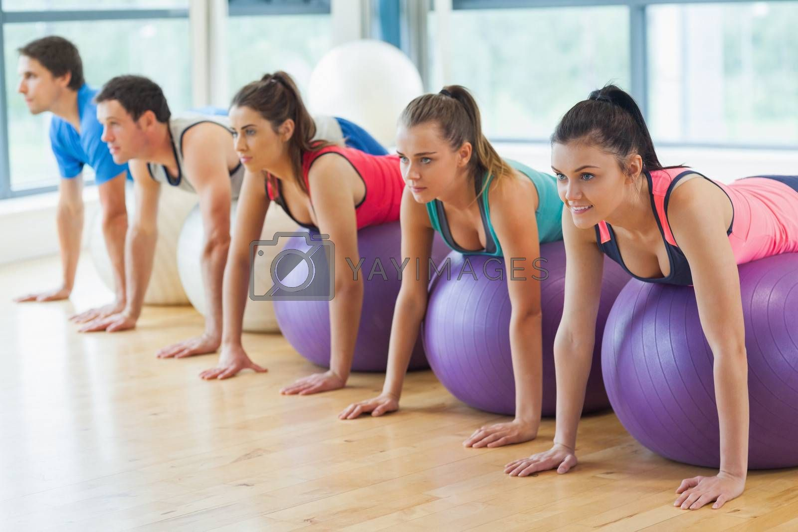 Side view of class exercising on fitness balls in a row at the bright gym