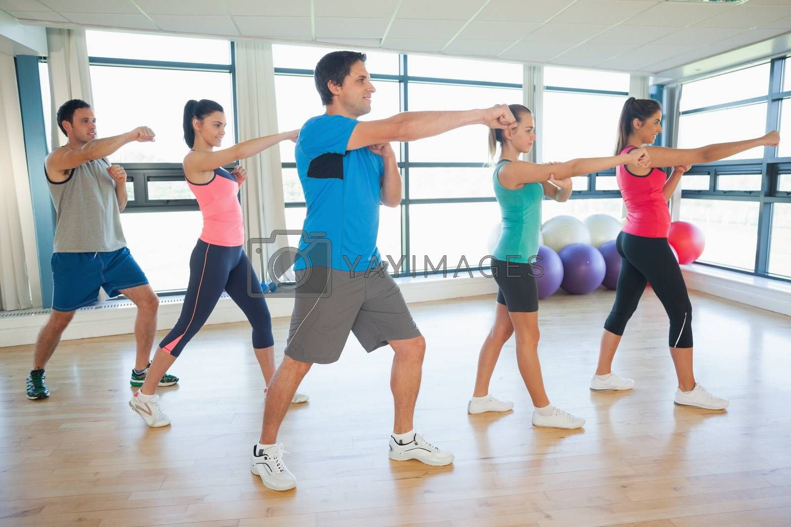 Full length of sporty people doing power fitness exercise at yoga class