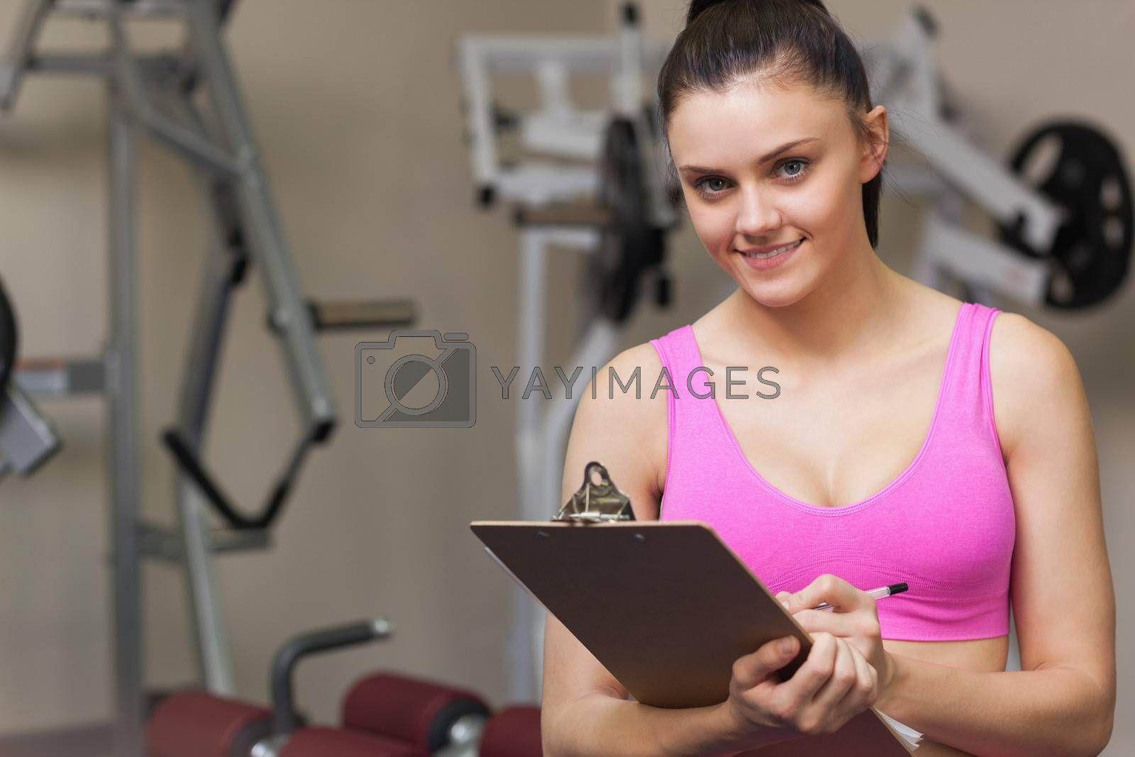 Portrait of a smiling female trainer writing on clipboard in the gym