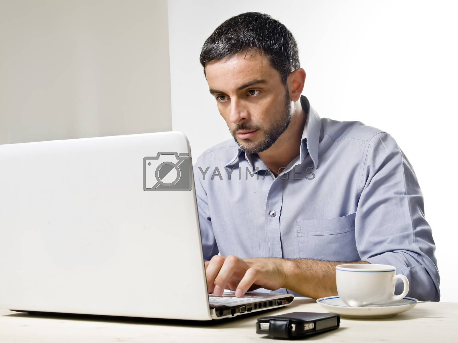 Young Man with Beard Working on Laptop isolated on a White Background