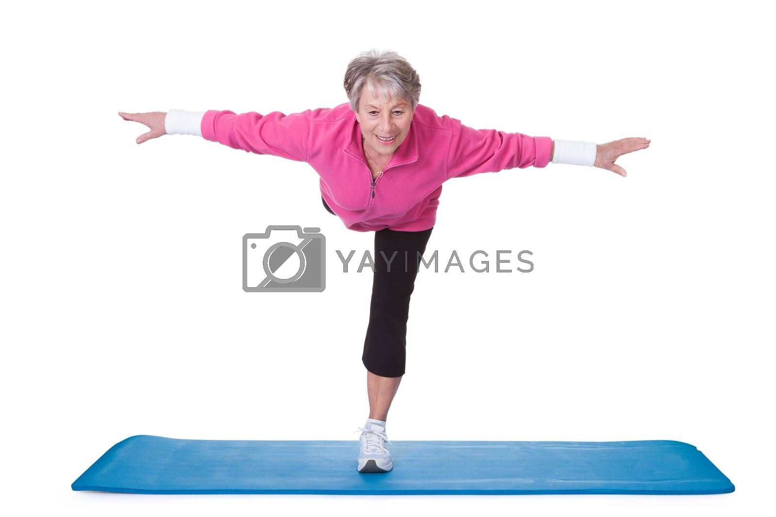 Senior Woman Standing On One Leg And Exercising Over White Background
