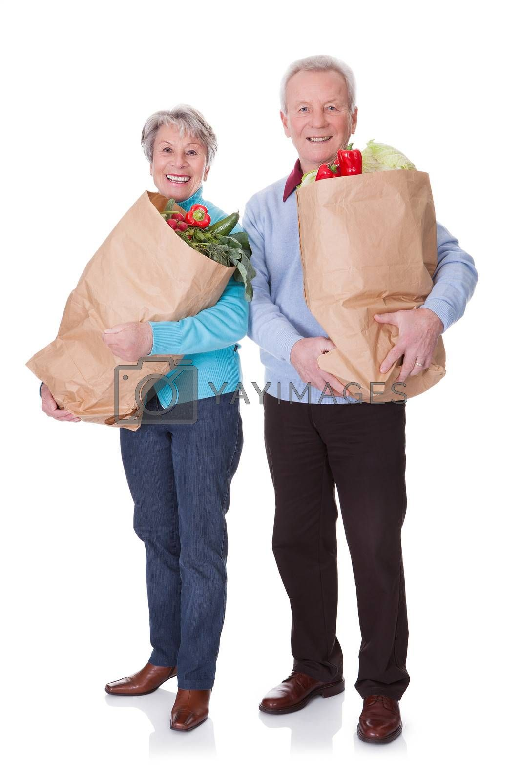 Portrait Of Happy Senior Couple Shopping Fresh Vegetables