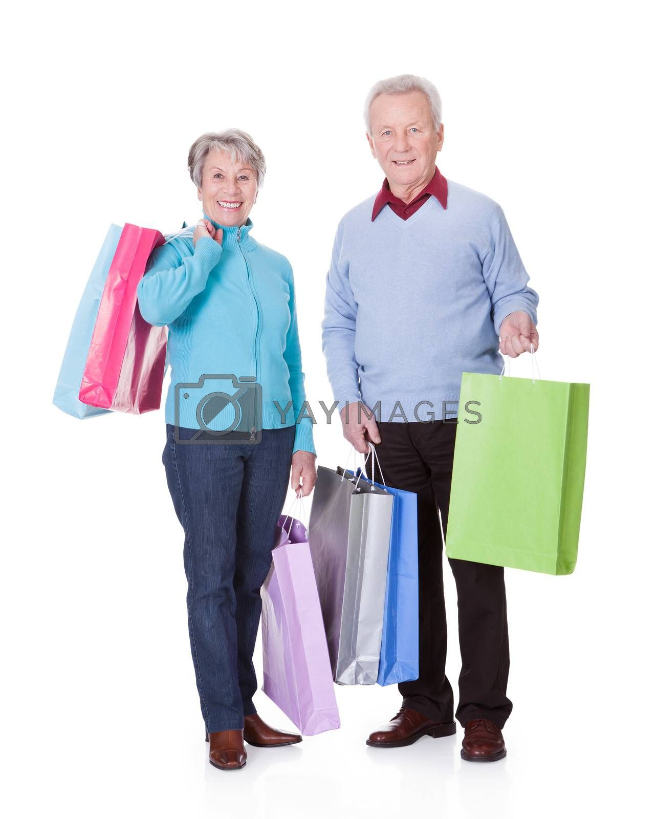 Portrait Of Happy Senior Couple Holding Shopping Bags