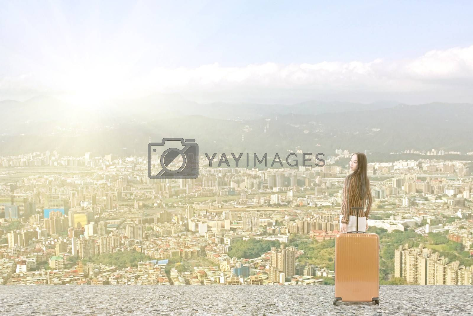 Modern Asian woman stand with a luggage in the roof of high building in the city.