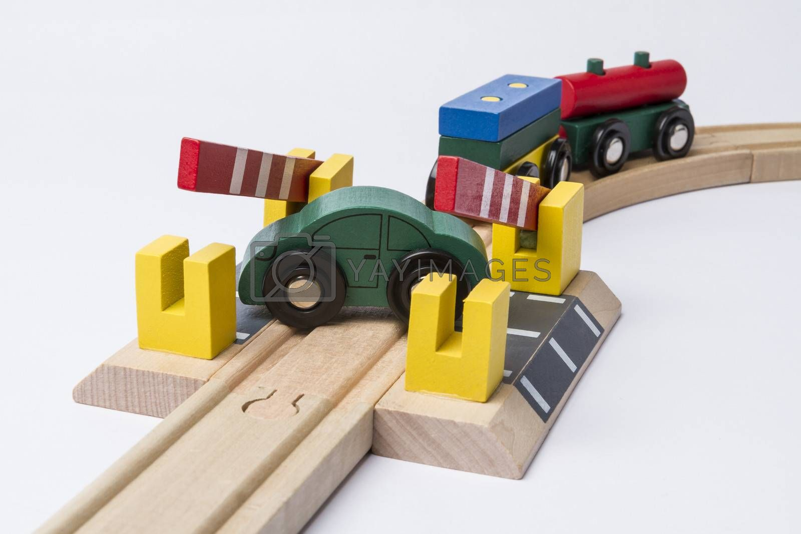 green toy car on railroad crossing with train coming