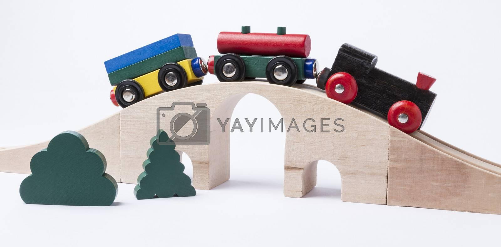 wooden toy train on bridge in grey background. horizontal image