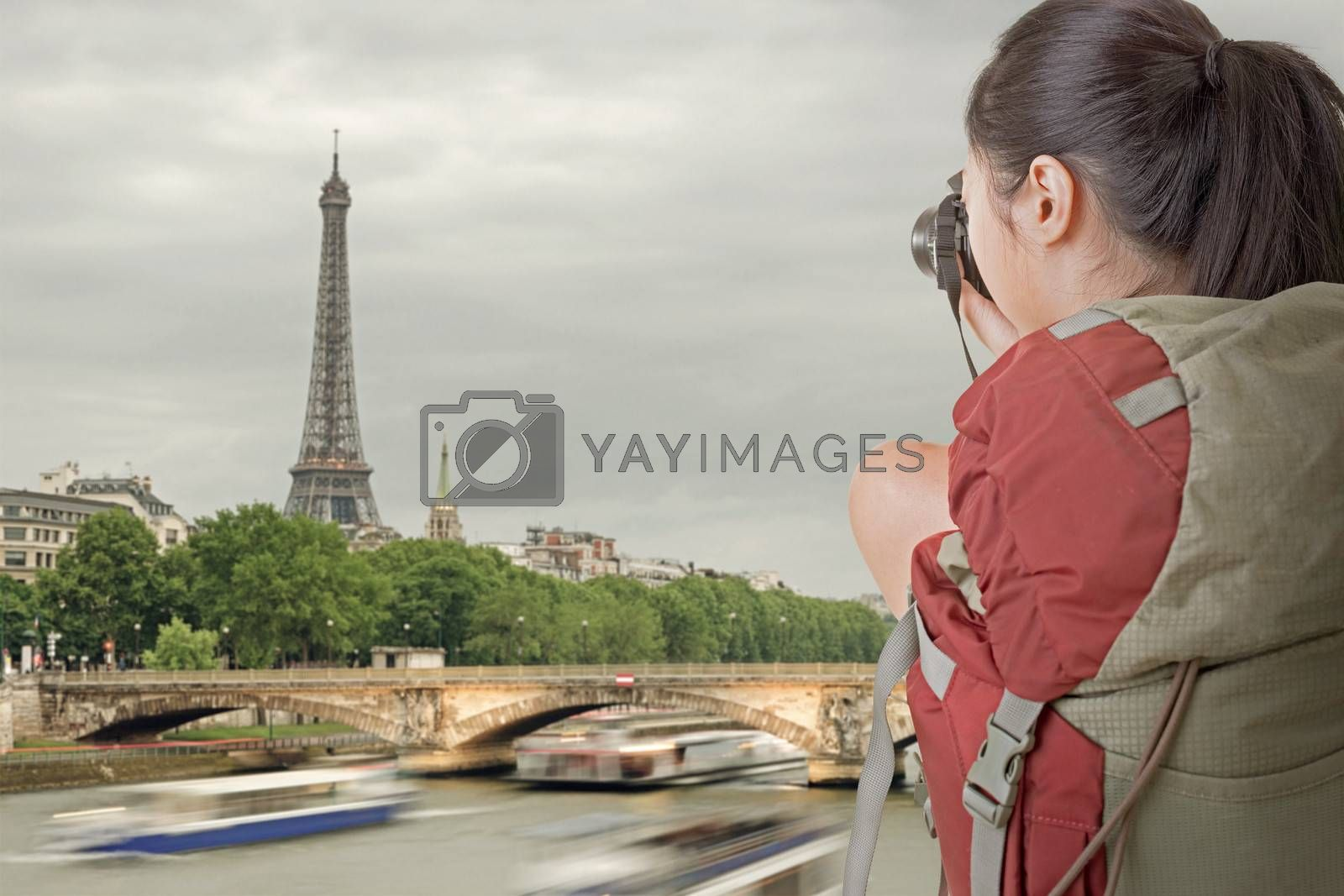 Young backpacker travel and take picture in Paris with famous Eiffel Tower.