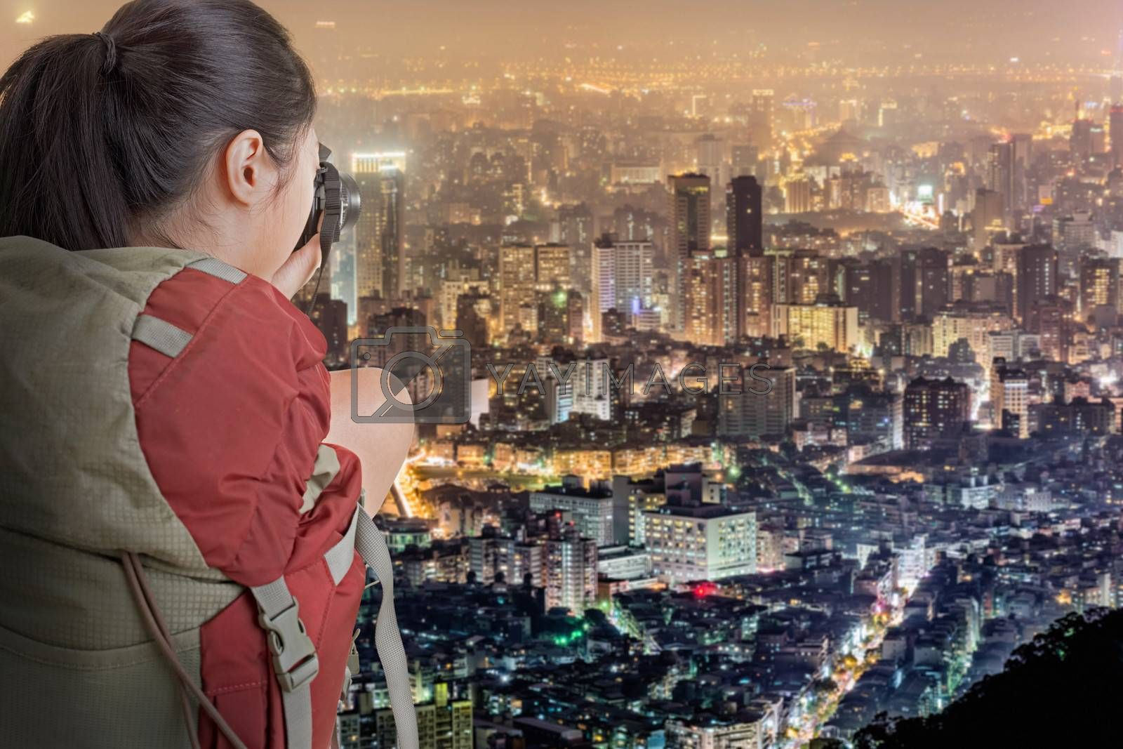 Young backpacker travel and take picture of city night scene in Taipei, Taiwan.