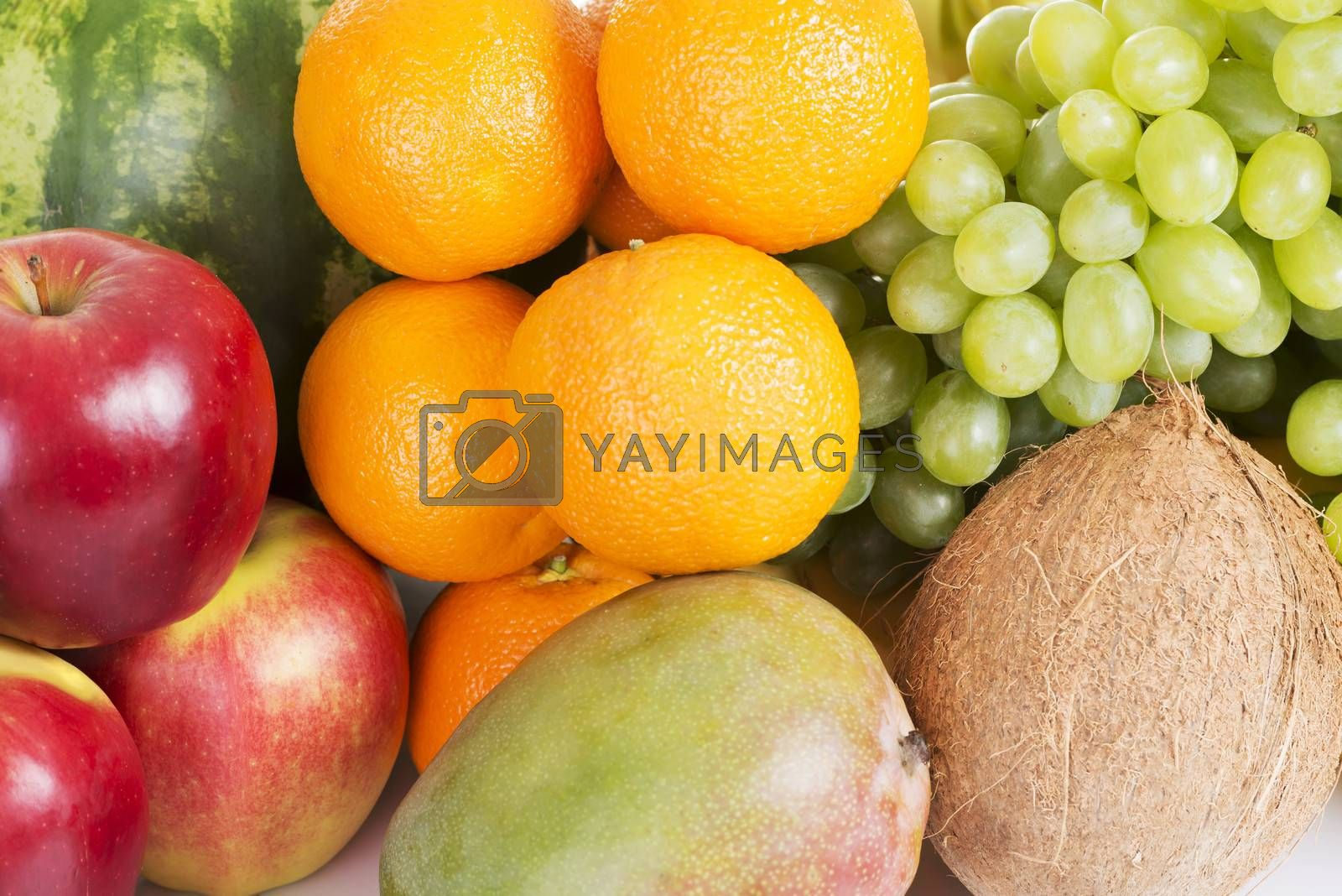 Close up on fresh fruits: mango, oranges,grapes, coconut,apples.