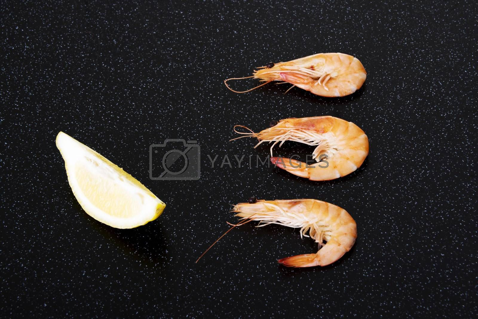 Fresh shrimps with lemon. On a kitchen table.