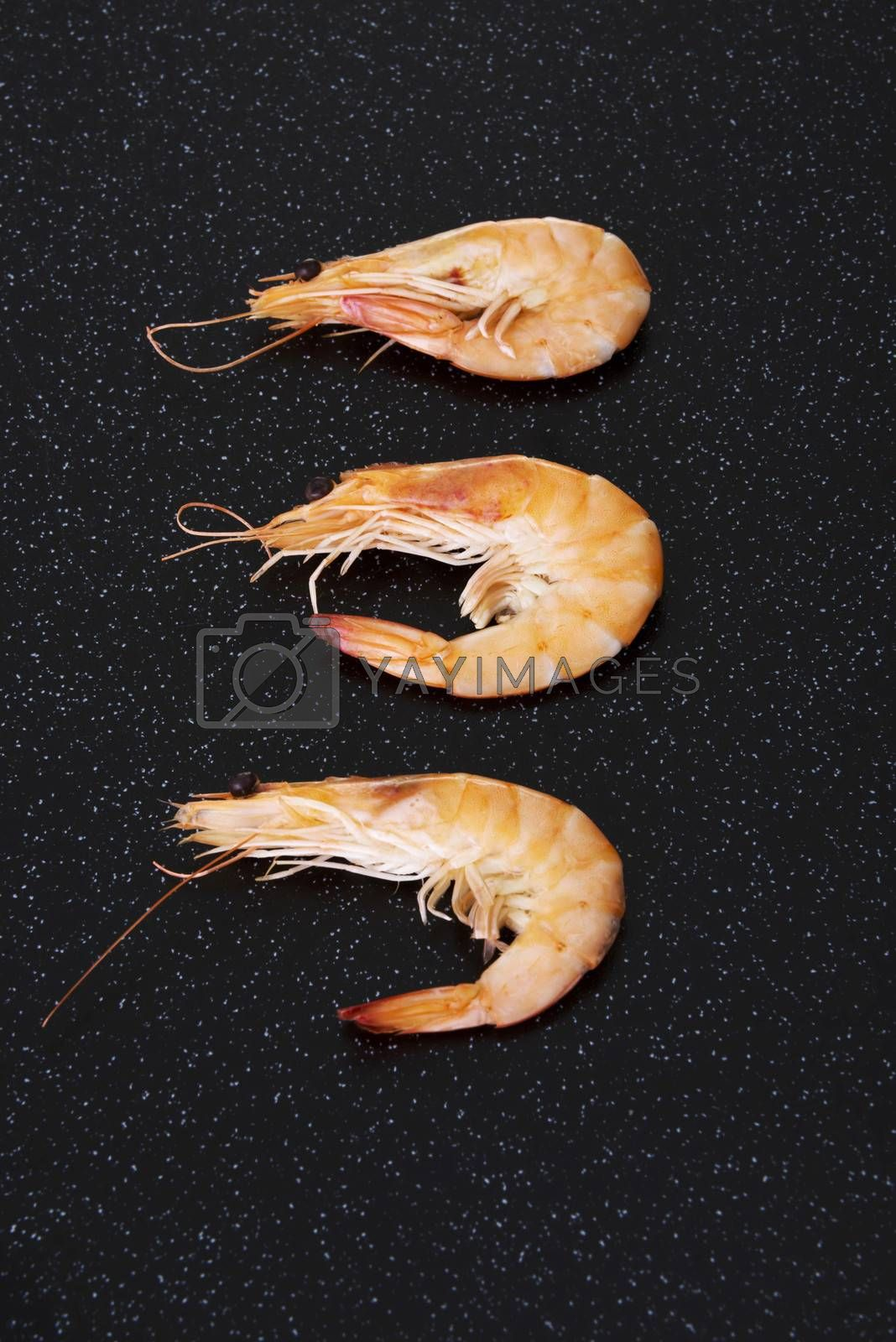 Three separated shrimps lying on a dark kitchen table.