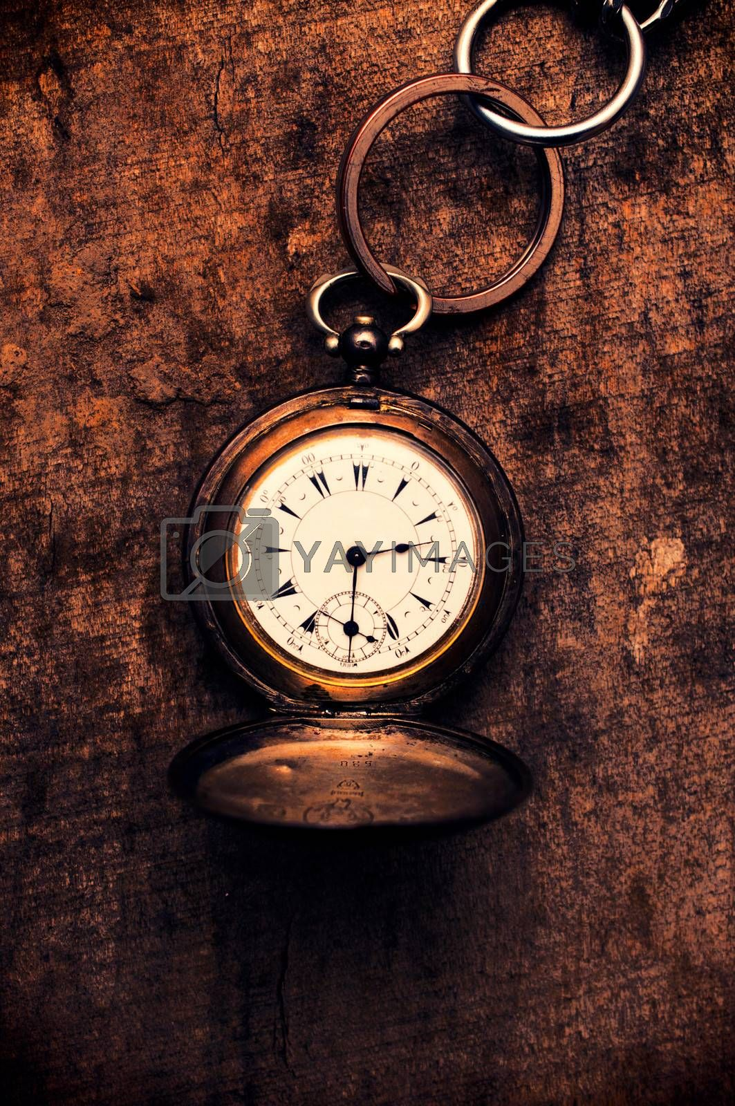 Old pocket watch on the wooden background from above