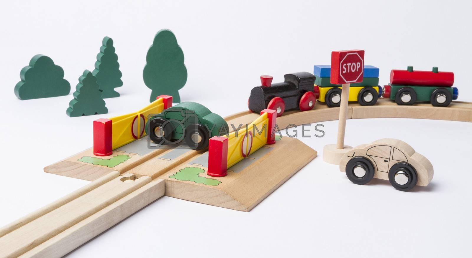 car on crossing with train coming. horizontal image. studio shot