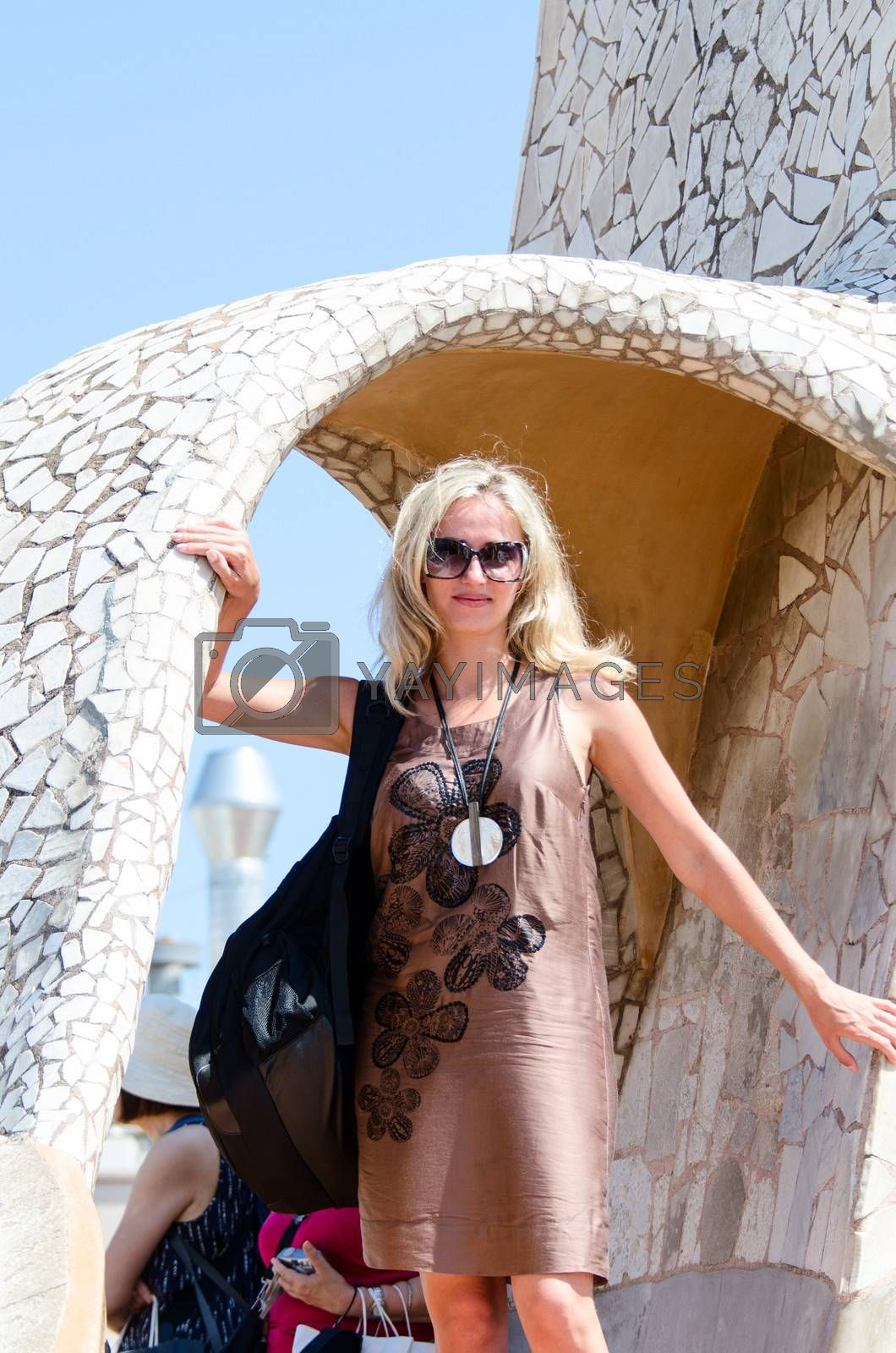 Tourist woman in sunglasses posing on Casa Mila, Barcelona, Spain