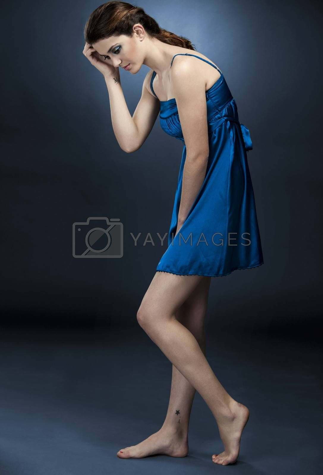 Sexy and beautiful fashion woman posing against a blue background