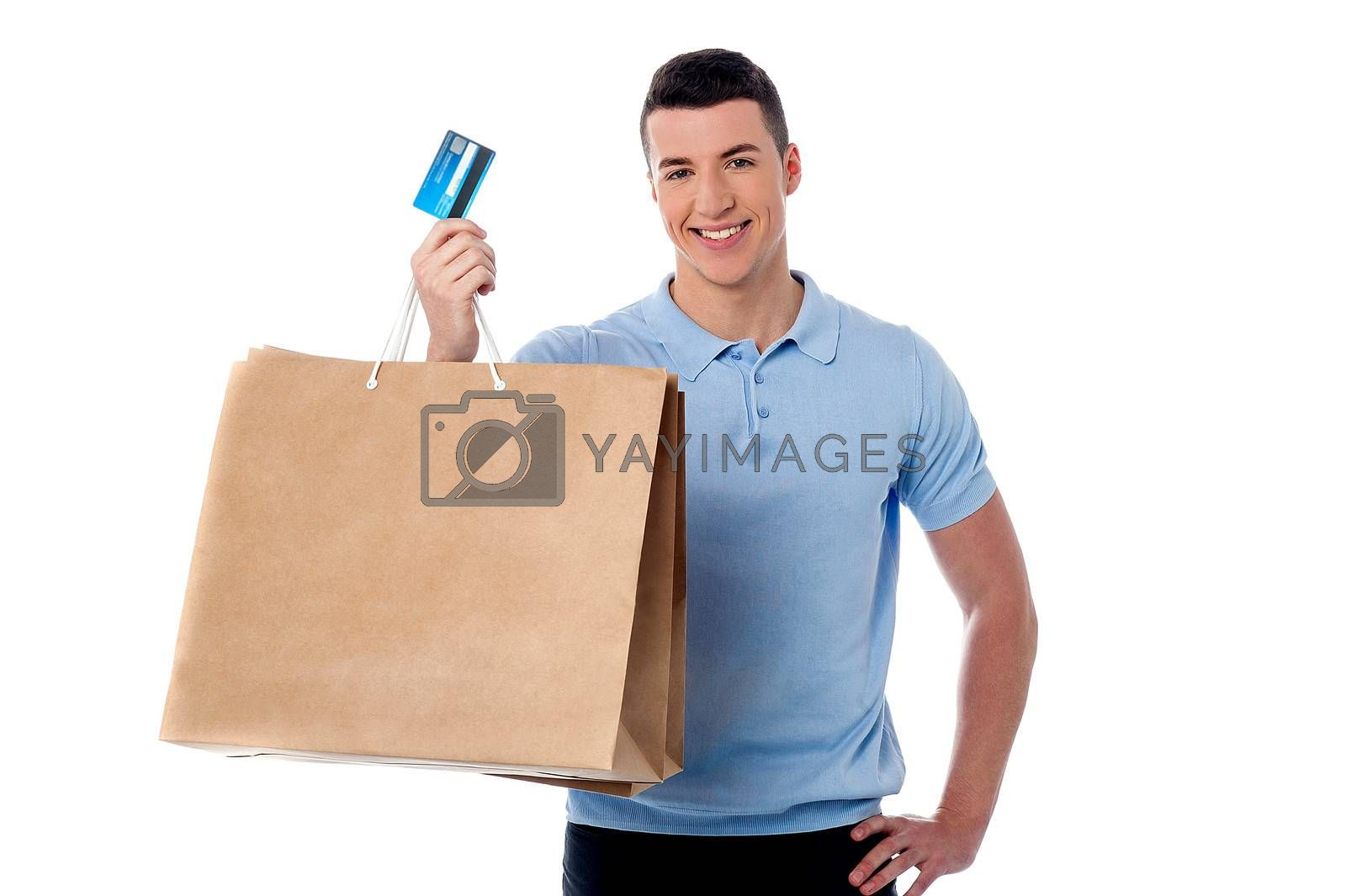 Young man showing his shopping bag and credit card