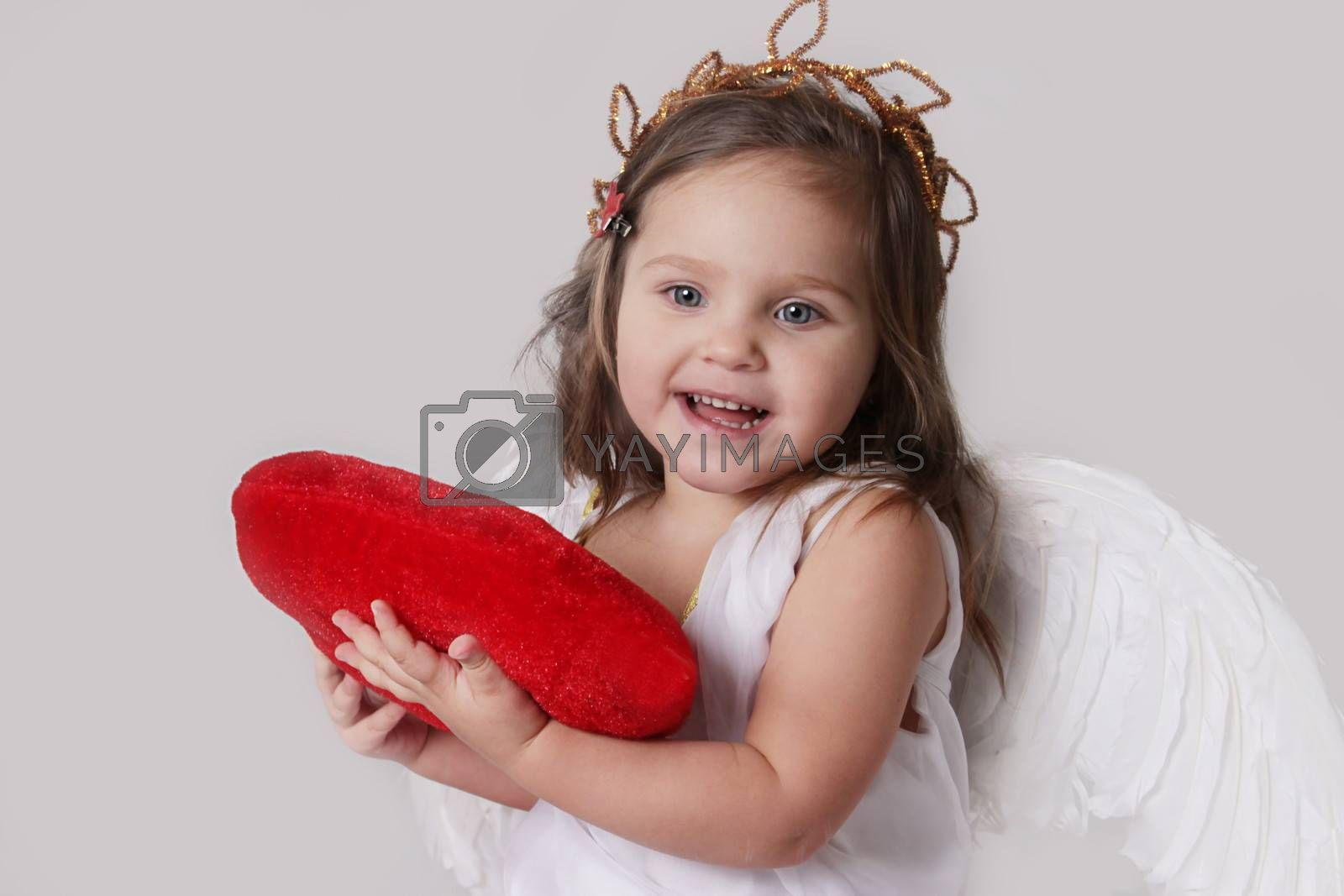 Happy cupid girl holds plush heart isolated on white